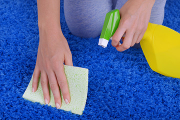 Cleaning carpet with cloth and  sprayer close up