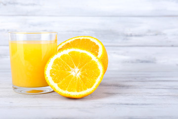 glass of juice with fresh orange on grey wooden table