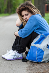 Sad girl with dreadlocks sitting on road