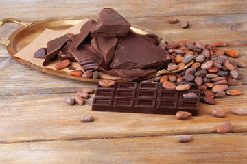 Cracked chocolate bar and cocoa beans on wooden background