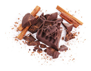 Cracked chocolate bar with spices isolated on white