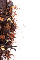Cracked chocolate bar with spices on white background