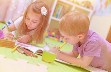 Happy baby boy & girl enjoying homework