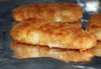 Breaded fish portions cooking on foil in the oven