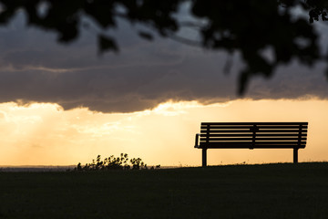 Silhouette bench facing out towards the sunset on a cloudy day