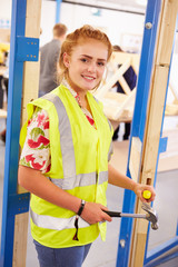 Female Student In Carpentry Class Fitting Door Lock