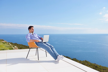 relaxed young man at home on balcony