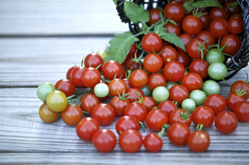 Cherry tomatoes in a basket on a wooden background