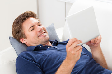 Man Using Digital Tablet While Lying On Sofa