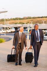 businessmen walking in airport parking lot