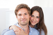 Man Giving Piggyback Ride To Woman At Home