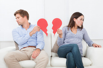 Couple Ignoring Each Other On Sofa