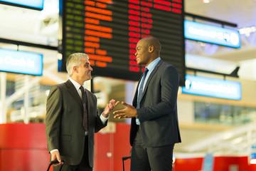 businessmen talking at airport
