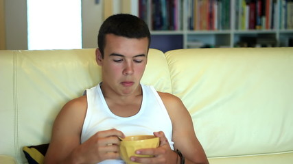teenager eating breakfast cornflakes while watching television