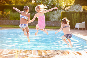 Group Of Girls Jumping Into Outdoor Swimming Pool