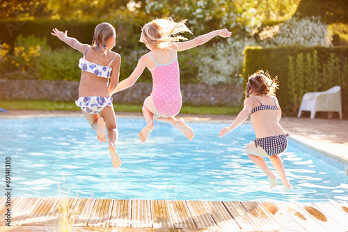 canvas print picture Group Of Girls Jumping Into Outdoor Swimming Pool