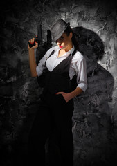Woman with hat and gun on grey wall