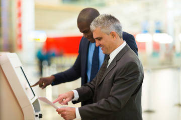 business travellers using self help check in machine at airport