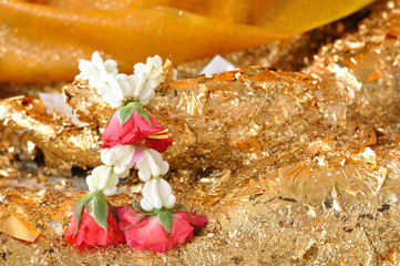 Beautiful garland-flower with rose hanging on Buddha statue.