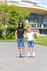 Mother and daughter on roller skates in summer