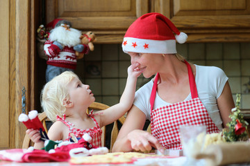 Mother and daughter preparing cookies of christmas