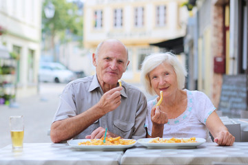 Happy senior couple eating in outdoors cafe