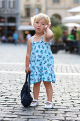 Cute little girl talking by mobile phone in urban environment