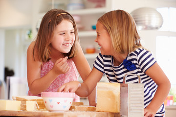 Girls Eating Ingredients Whilst Making Cheese On Toast