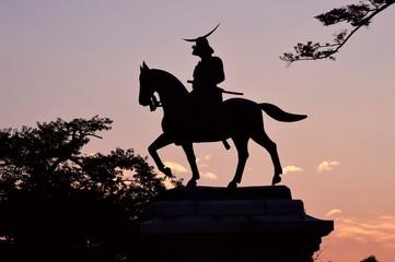夕焼けの空に伊達政宗騎馬像