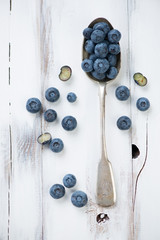 Spoon with blueberries over wooden background, view from above