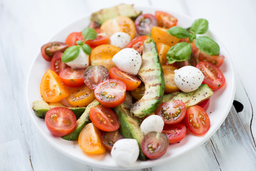 Plate with grilled avocado, tomatoes, mozzarella and basil salad