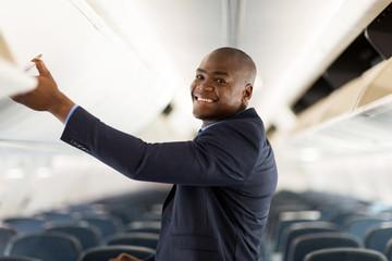 african american businessman opening overhead locker on airplane