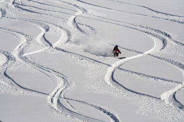 Mountain skier go down on powder snow.
