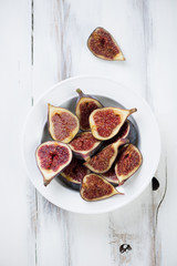 Above view of ripe sliced figs in a glass plate, vertical shot