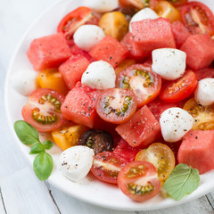 Salad with watermelon cubes, tomatoes and mozzarella, close-up
