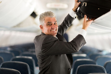 middle aged business traveler putting luggage into overhead lock