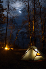 Tourist camping with bonfire at night