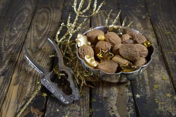 Walnüsse mit Nußknacker als Weihnachtsdekoration in braun gold