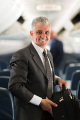 middle aged businessman carrying bag on airplane