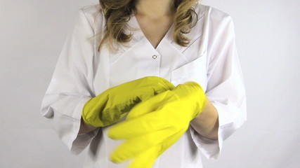 Woman in white robe smock put on yellow rubber gloves on hands