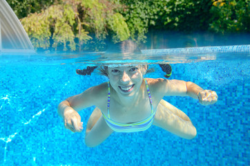 Child swims in swimming pool, underwater and above view