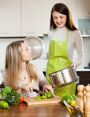 Two women cooking  with vegetables