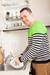 Smiling man washing plates