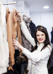 woman choosing jacket at clothing store