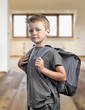 Young boy with backpack isolated on white background
