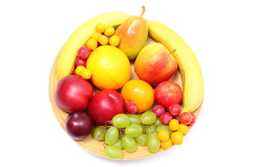 Fresh ripe fruits on wooden plate