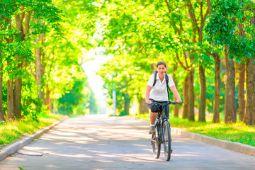 young girl on a bicycle in a park in the early morning