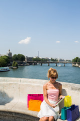 Young woman in Paris with shopping bags using digital tablet
