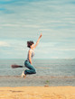 Happy woman with broom jumping on the beach
