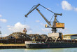 Harbor - crane loading a ship with scrap metal - 69153716